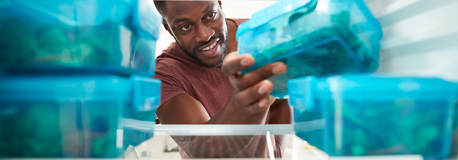 Man reaching into fridge for healthy meal in blue conta